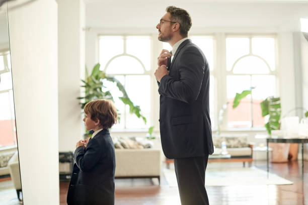 Shot of an adorable little boy and his father getting dressed in matching suits