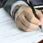 Business Man writing on forms